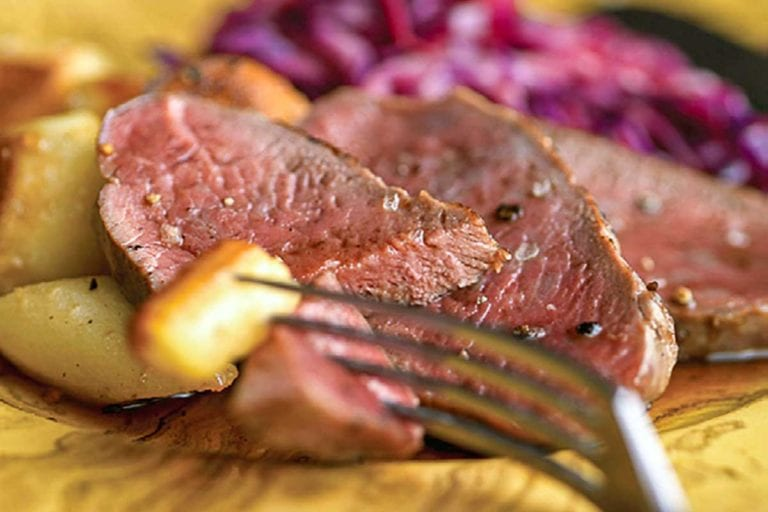Slices of cider-basted venison with roasted potatoes and red cabbage on a yellow plate.