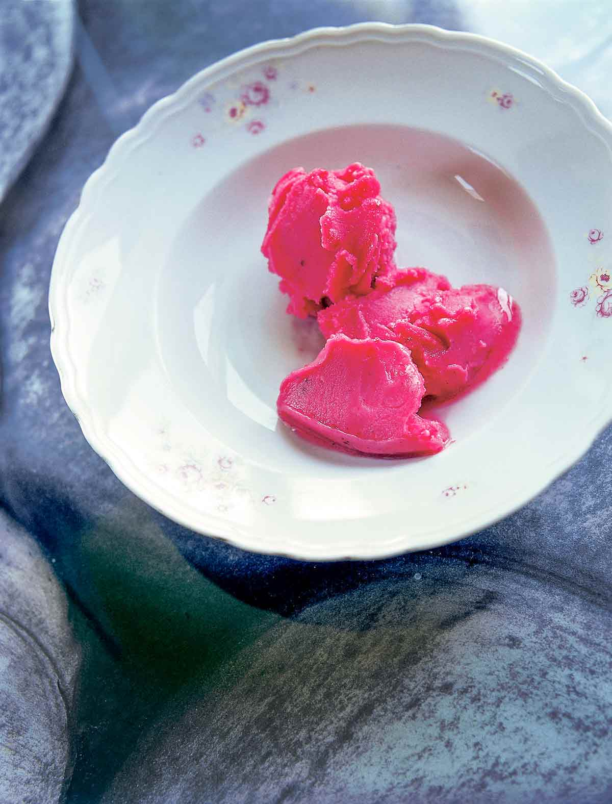 A few dollops of cranberry sorbet in a white porcelain bowl.