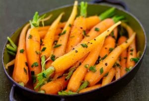 Oval pan with cumin-scented carrots sprinkled with chopped chives, orange zest, and pepper