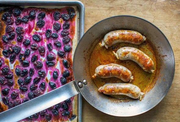 Skillet with four seared pork sausages near a baking sheet of roasted grapes