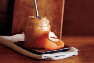 A jar of roasted applesauce with a spoon resting inside on a saucer with a strip of apple peel.