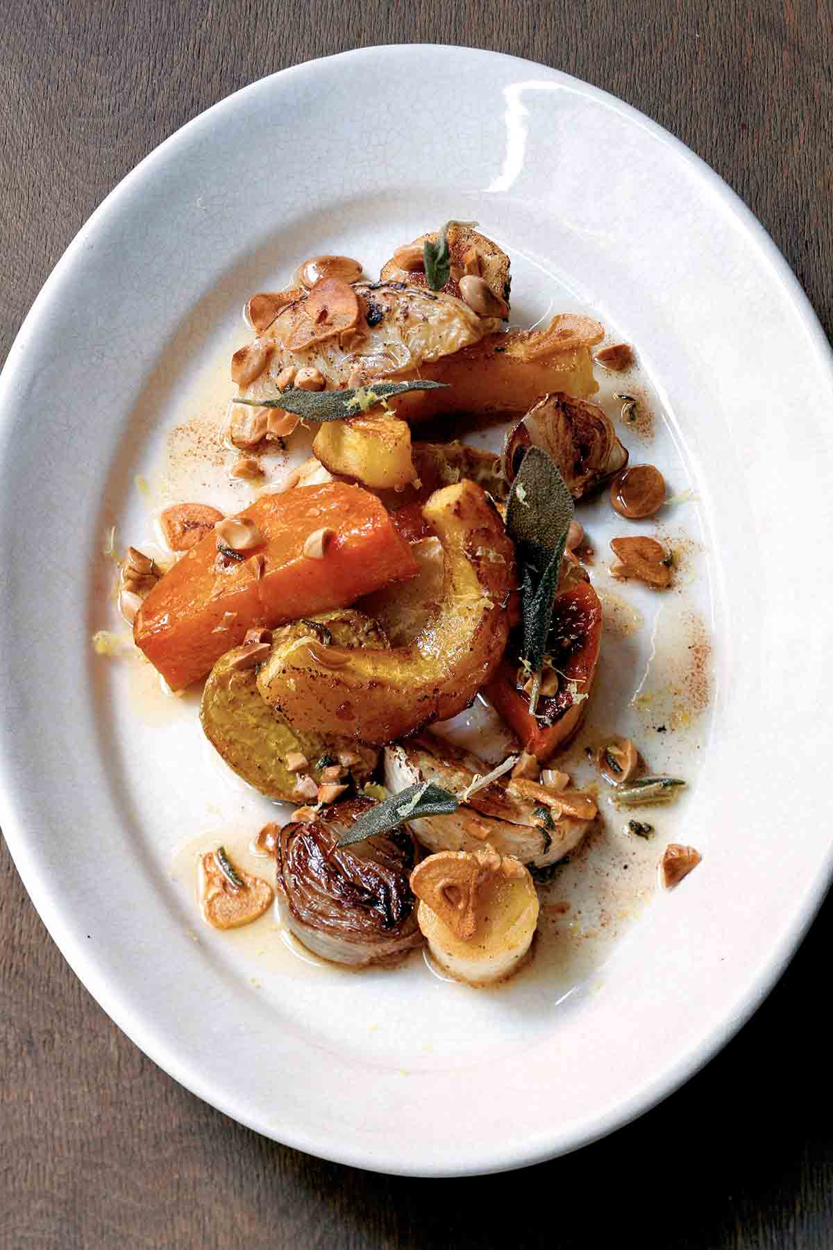 A white oval platter filled with roasted root vegetables and Marcona almonds, drizzled with sage-garlic brown butter.