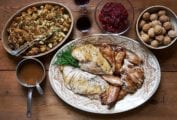 An oval platter with roasted and braised turkey, a dish of stuffing, a bowl of cranberry sauce, a bowl of chestnuts, two glasses of wine, and a small pot of gravy on a wooden table.
