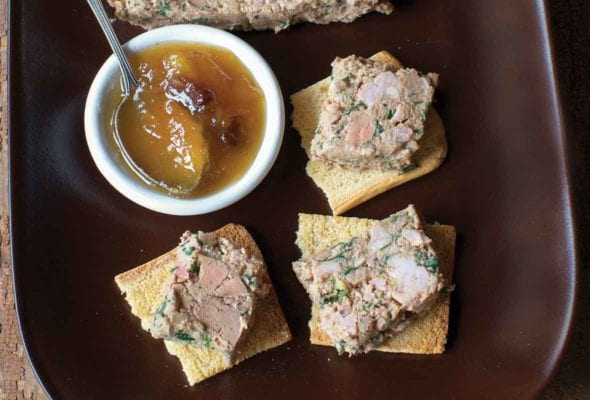 Wedges of Arlington chicken liver pate on top of crisp crackers on a brown serving platter along with a small bowl of chutney.
