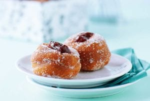 A white plate with two jelly-filled doughnuts