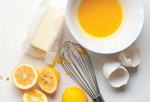 Bowl of yellow lemon curd, whisk, stick of butter, egg shells, halved lemons