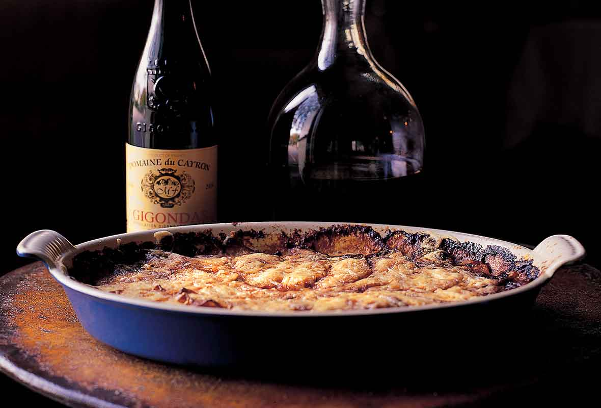 A blue gratin dish filled with potato gratin and a two wine bottles in the background