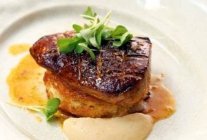 A plate with a large piece of seared foie gras topped with watercress and apple puree on the side.