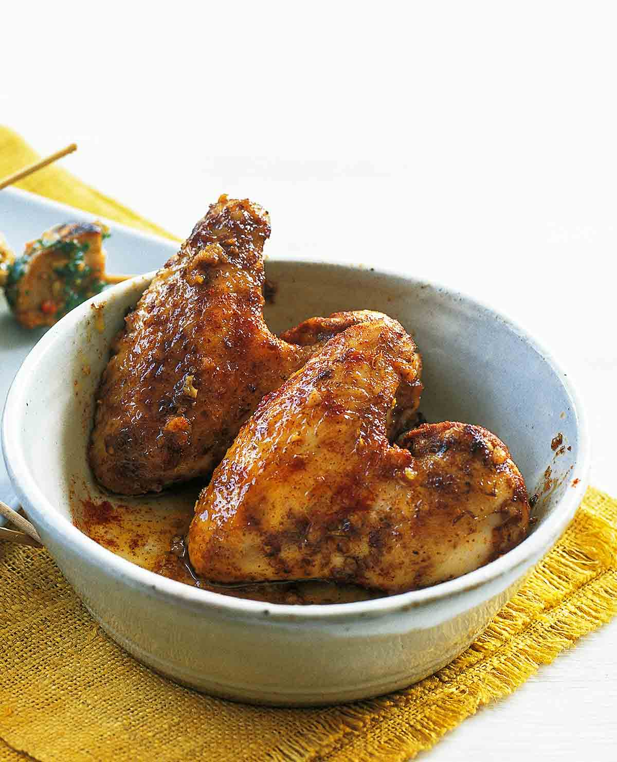 A white bowl with two chicken wings with garlic and paprika on a yellow placemat.