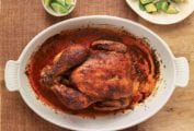 Chicken roasted red with paprika in a casserole dish and plate of lime wedges on a wooden table