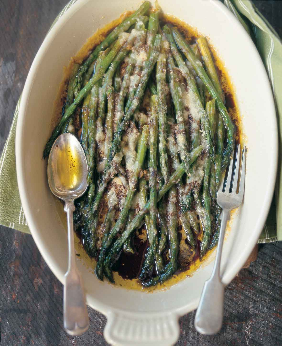 An oval serving dish filled with baked asparagus with Parmesan and balsamic vinegar with a fork and spoon resting on top.