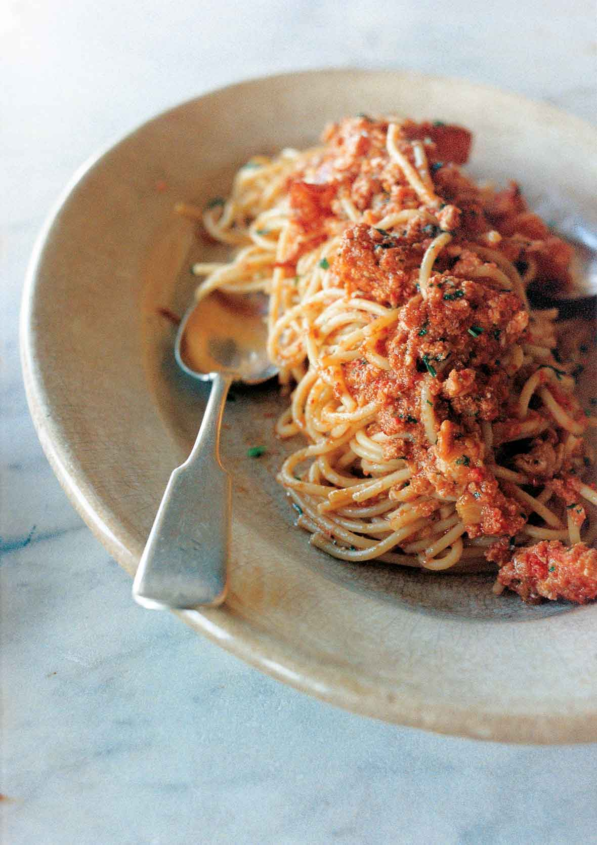 A serving of lobster fra diavolo in an oval bowl with a spoon resting inside.