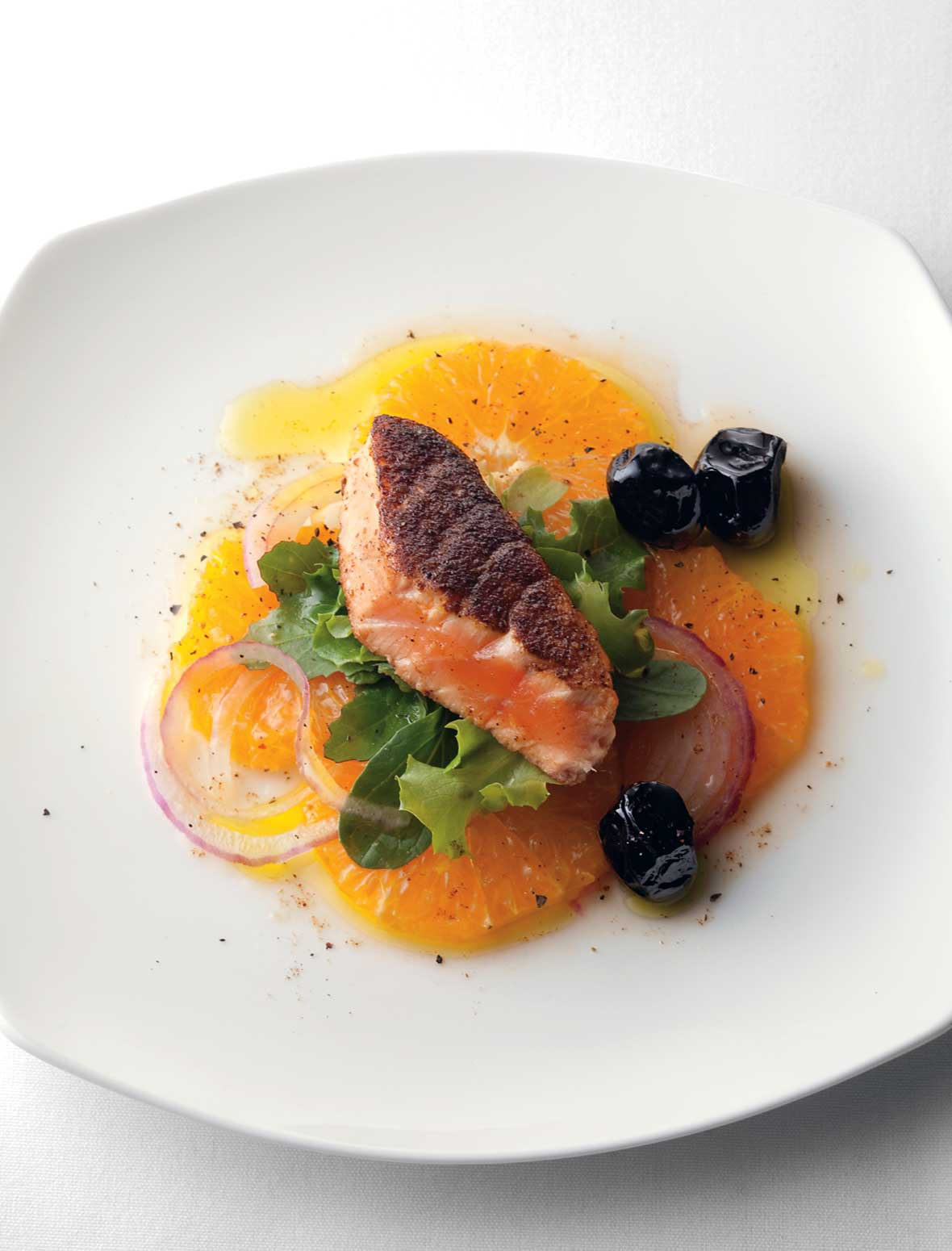A white plate with a piece of pan-seared Moroccan salmon on a bed of orange slices, red onion, and greens with three black olives on the side.