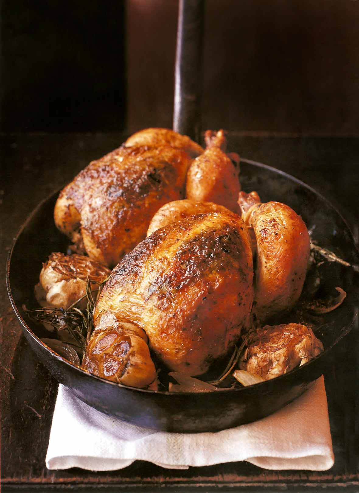 Two whole chickens and whole garlic heads in a cast iron pan