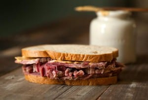 Several slices of homemade corned beef in a sandwich on a wooden table.