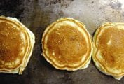 Three light and fluffy pancakes on a griddle