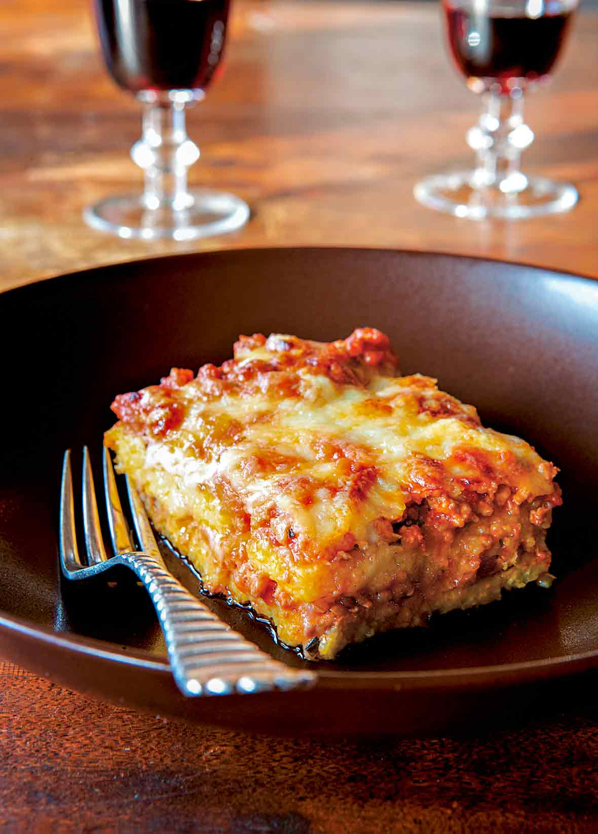 A square of polenta with layers of meat sauce on a plate with a fork, two glasses of wine