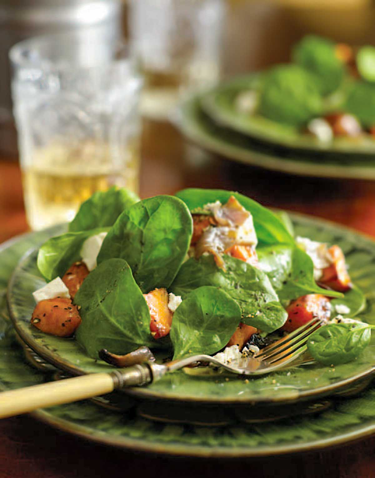 A serving of roasted sweet potato and feta salad on a green plate with a fork resting on the plate.