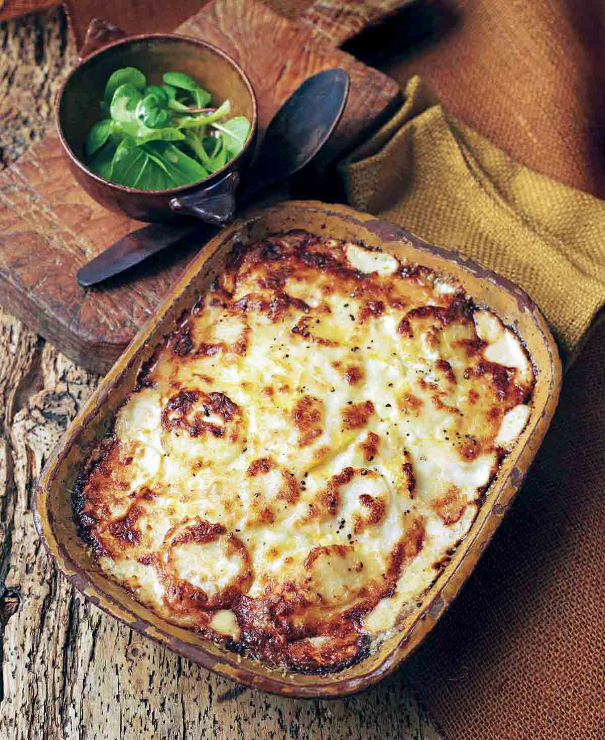Casserole dish of root vegetable gratin topped with bubbly brown cheese on wood table