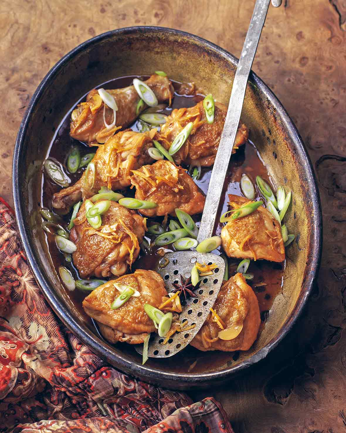 A crock filled with browned chicken thighs and sliced scallions, a spatula in the middle
