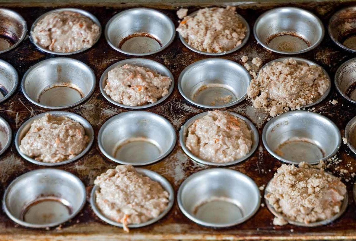 A muffin tin half filled with uncooked carrot cake muffins.