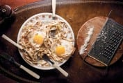 A tangle of brown butter pasta, toasted pine nuts, and two fried eggs on a plate with three forks in it.