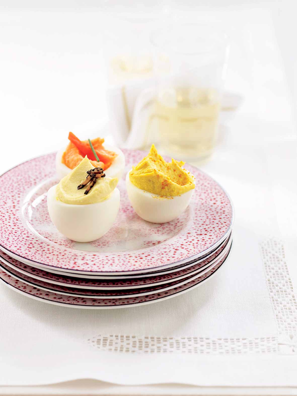 A plate with a horseradish deviled egg, truffled deviled egg, and smoked salmon deviled egg