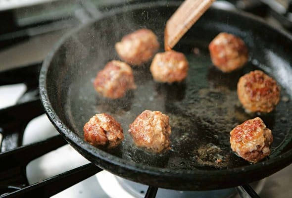 A cast-iron skillet with eight cheater's chorizo meatballs being cooked in it.
