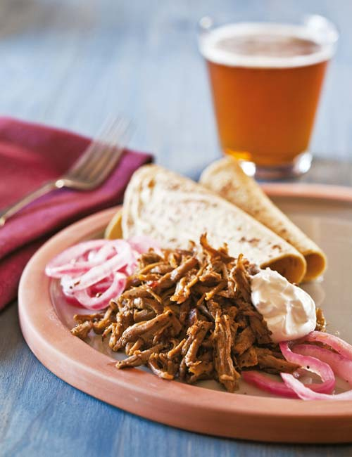 A pile of pulled pork and pickled onions for pulled pork tacos with habanero sauce.