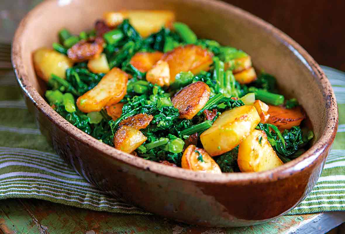 Pieces of sauteed broccoli rabe and slices of seared potatoes in a brown oval dish on a green bench