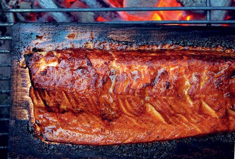 Half of a whole salmon on a cedar plank over glowing coals.