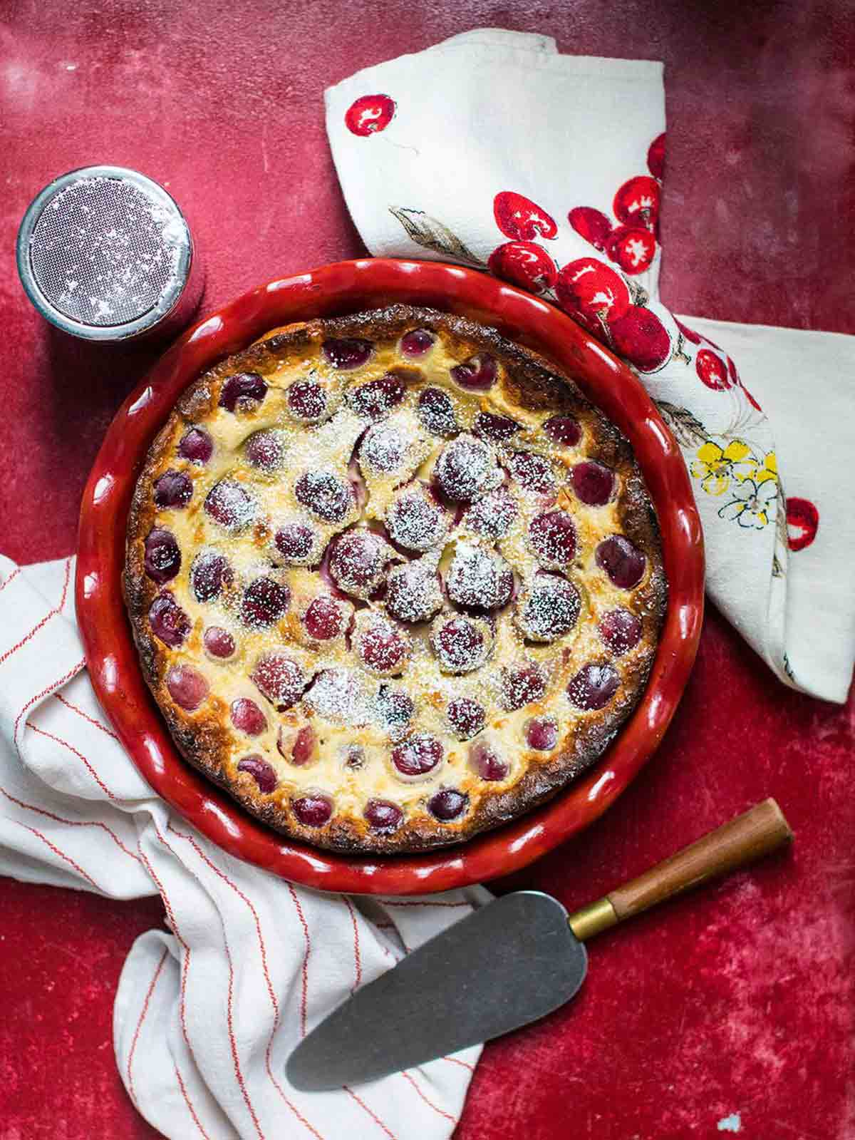 A cherry clafouti in a red dish with cherry dish towels