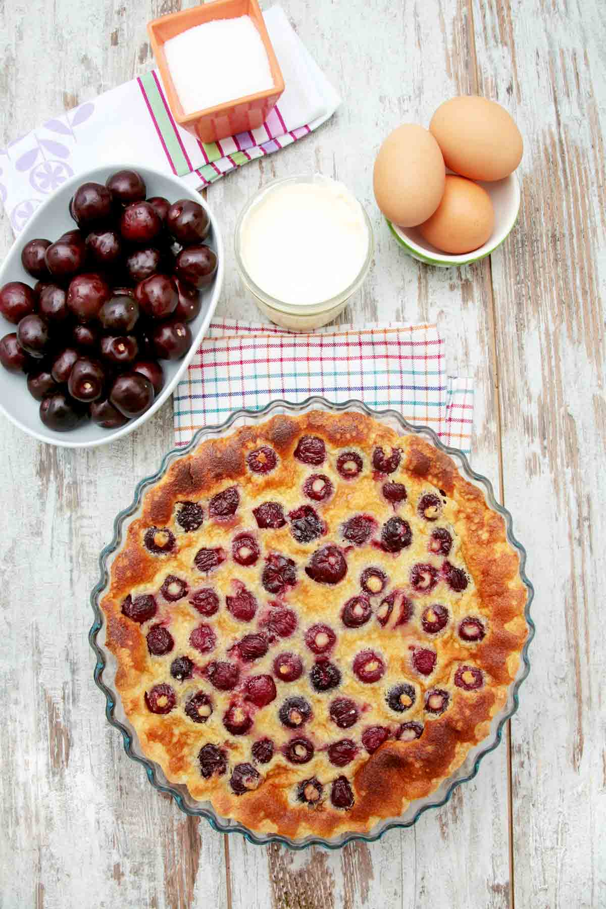 A cherry clafouti and dishes of cherries, eggs, milk, and sugar.