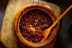 A bean pot of baked beans with a wooden spoon placed on a wooden chair