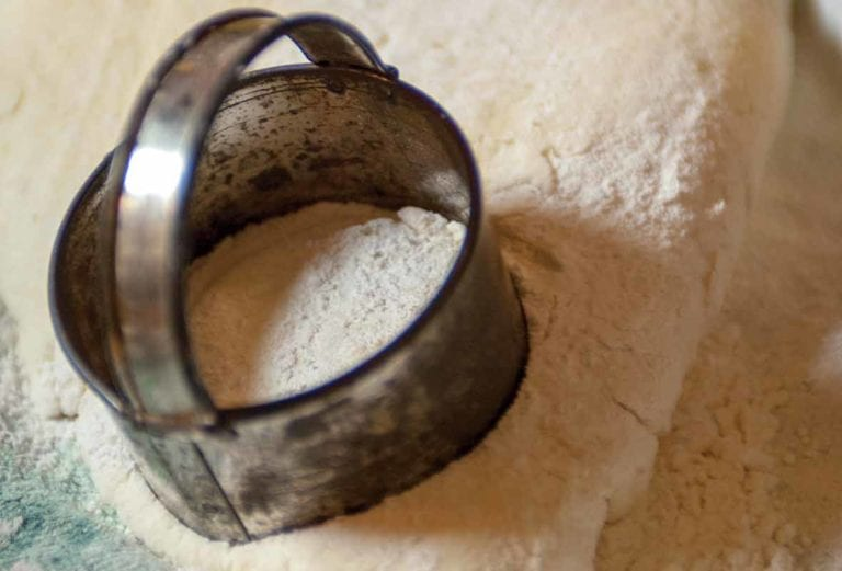 A woman's hand using a biscuit cutter on cream biscuit dough