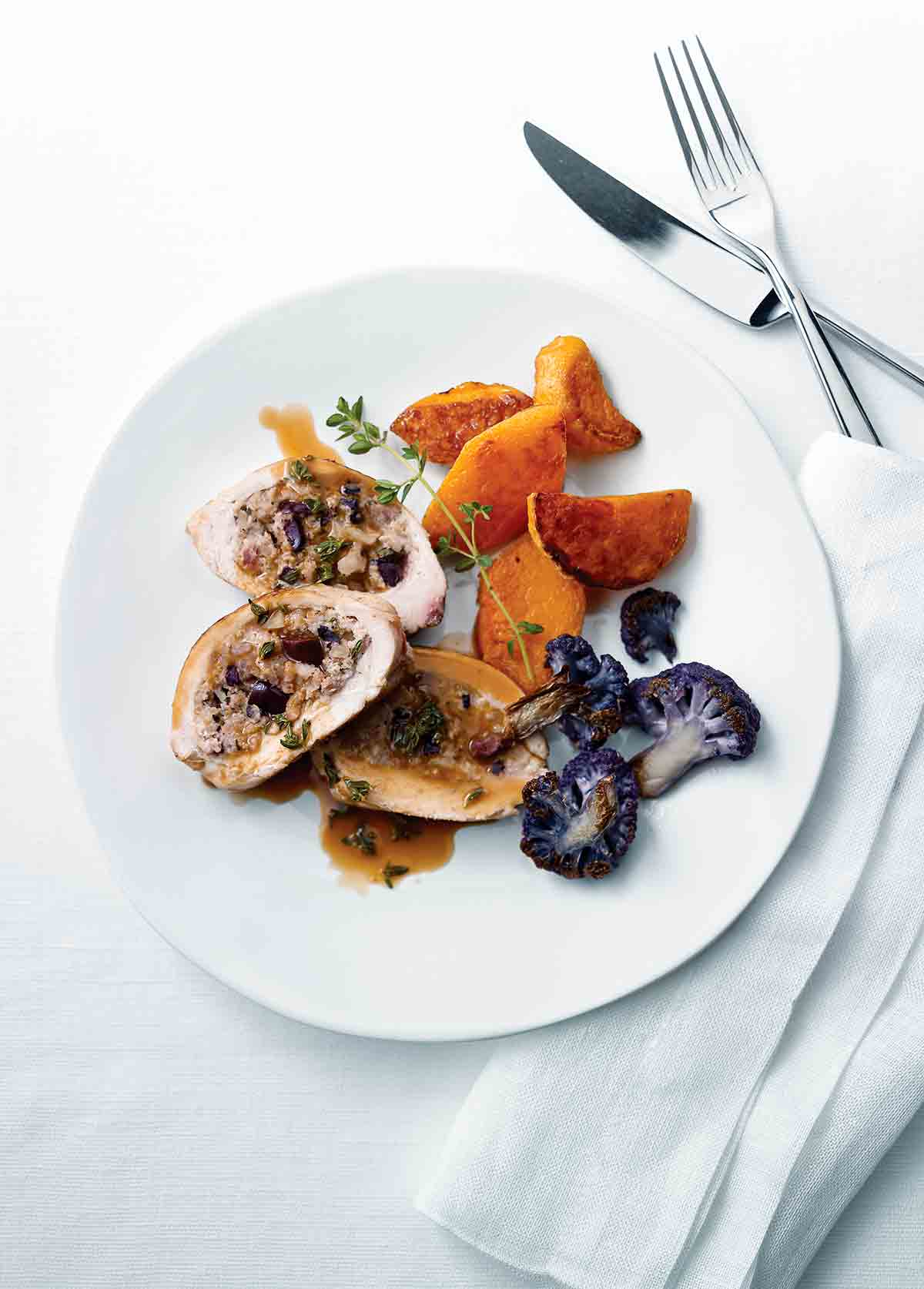 A sliced Mediterranean-style stuffed chicken breast on a white plate with purple cauliflower, sweet potato, and a sprig of thyme.
