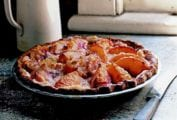 A peach and crème fraîche pie sitting on a window sill with a pitcher nearby