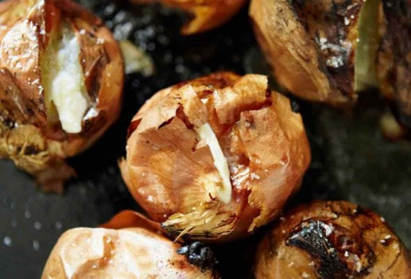 Several whole roasted onions with crispy skin and creamy flesh.