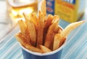 A blue paper cup filled with beach fries that are sprinkled with Old Bay seasoning.