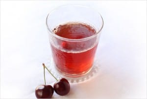 A glass filled with cherry spritzer and two cherries beside it.
