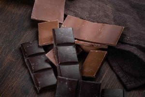 Pieces of dark and milk chocolate on a brown cloth and wood table in answer to the question of which chocolate: milk or dark?.