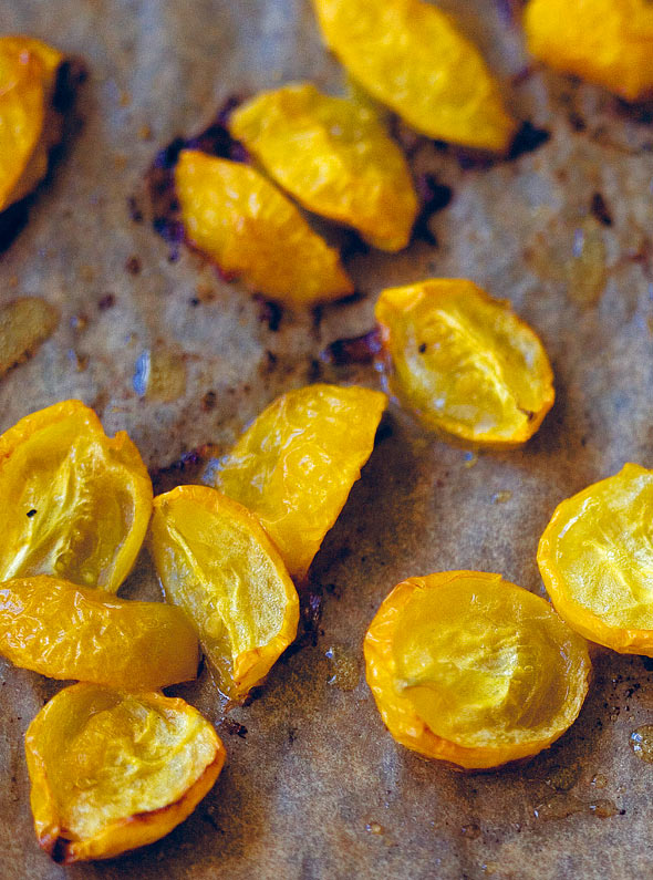 Cut yellow roasted cherry tomatoes on a sheet of parchment paper.