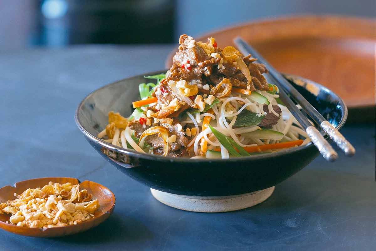 A bowl filled with Vietnamese beef and rice noodle salad, with chopsticks resting on the bowl, and a small dish of peanuts beside it.