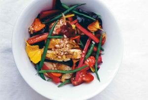 A white bowl filled with warm chicken with green beans and chard, topped with edible flowers.