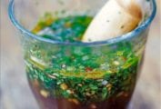 A glass full of chimichurri--an Argentine steak sauce--made with vinegar, olive oil, parsley, oregano, garlic, red pepper flakes