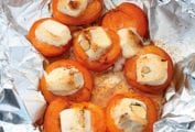 An open foil packet on the grill filled with grilled apricots with gooey nougat in the center.