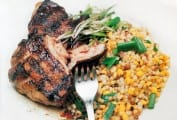 A piece of grilled guinea hen with sweet corn fregula beside it, all topped with chopped scallions.