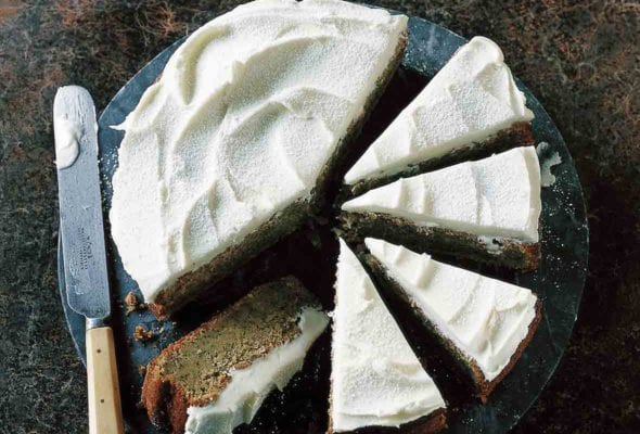 A zucchini cake with lemon and poppyseed topped with lemon frosting on a platter with half the cake cut into slices.