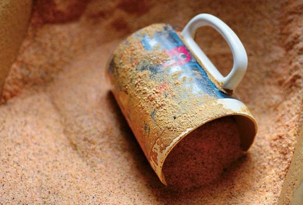 A mug lying on its side in a bin of cajun spice mix