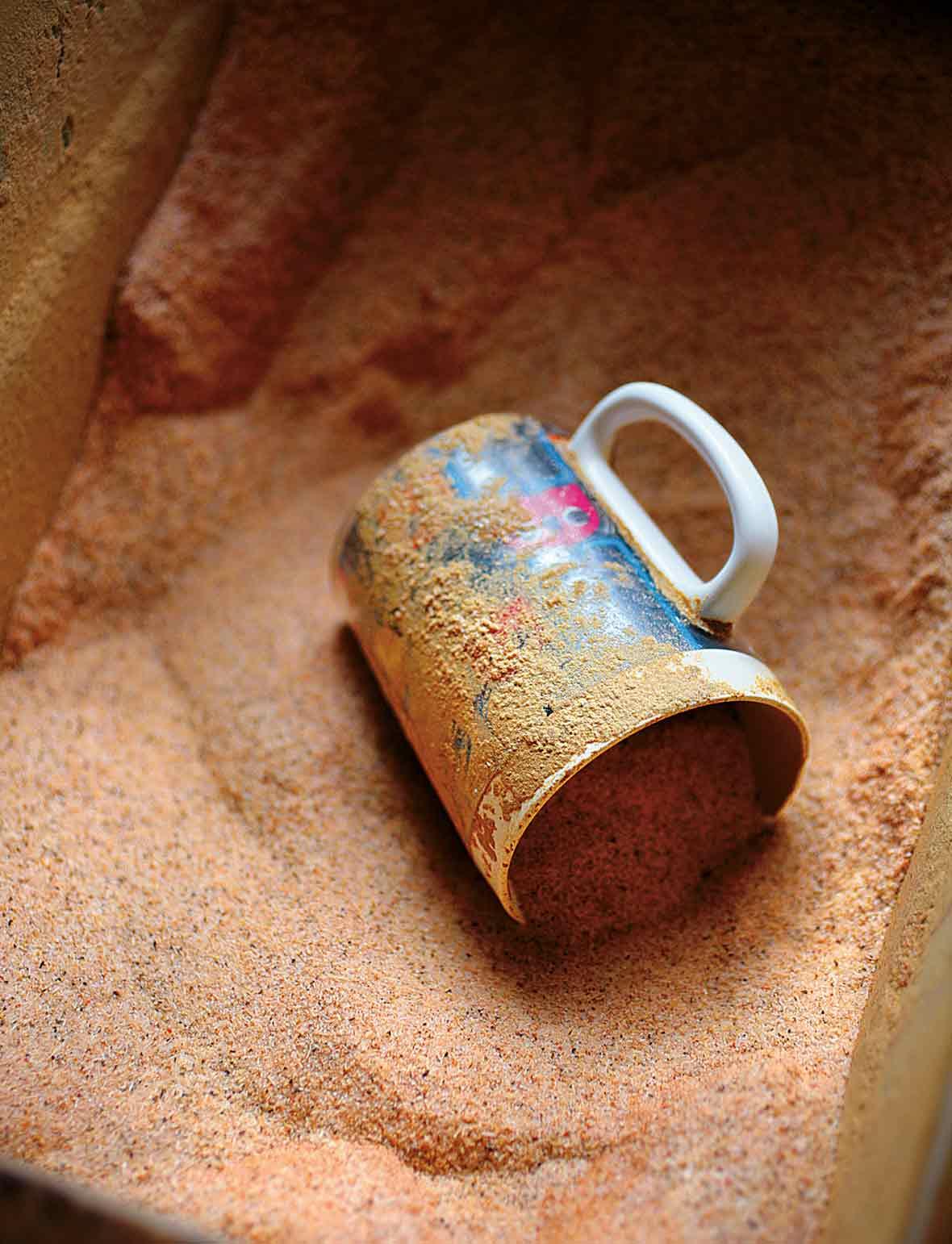A mug lying on its side in a bin of cajun spice mix